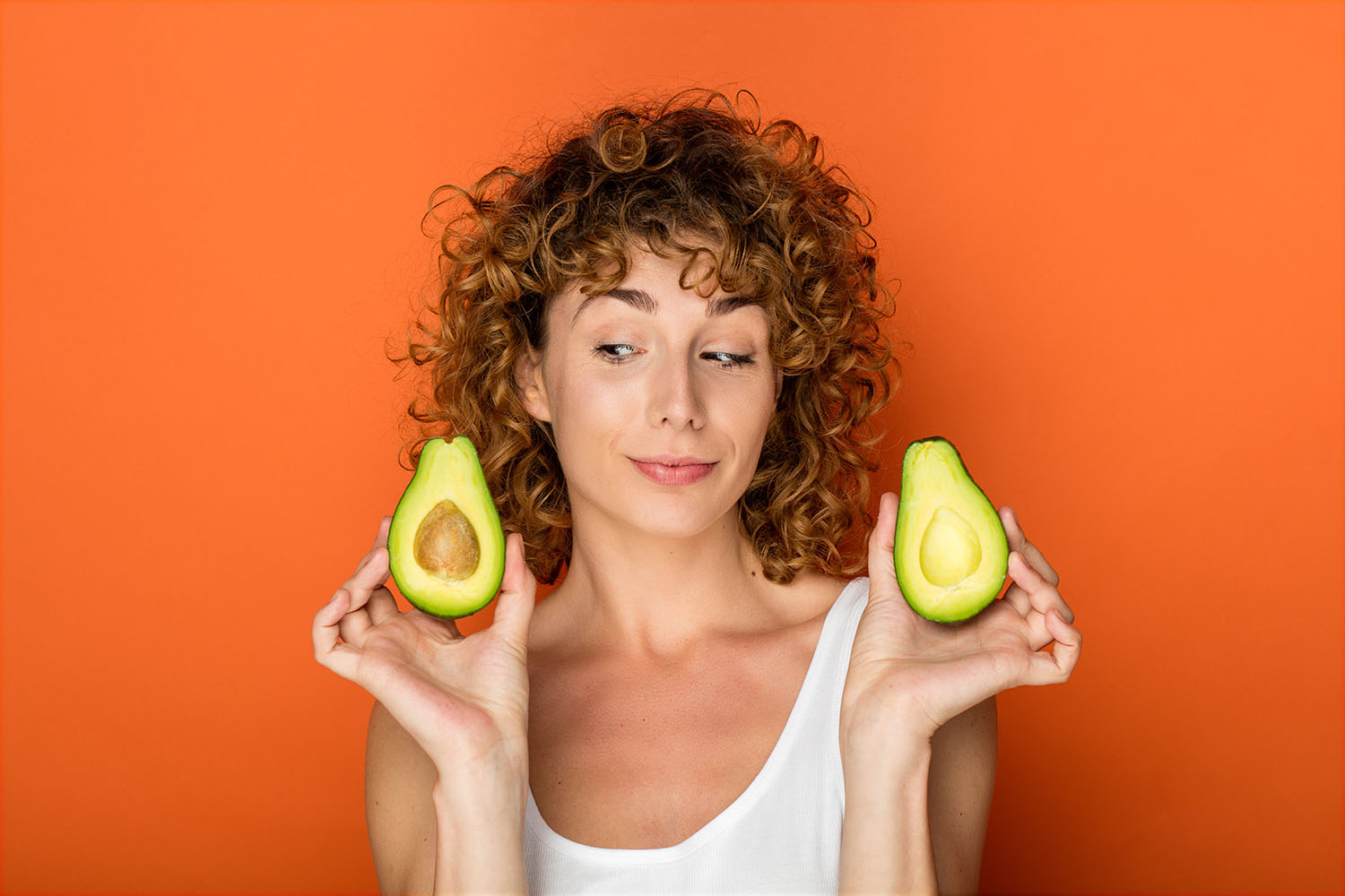 Young curly haired woman holding an avocado in front of orange background