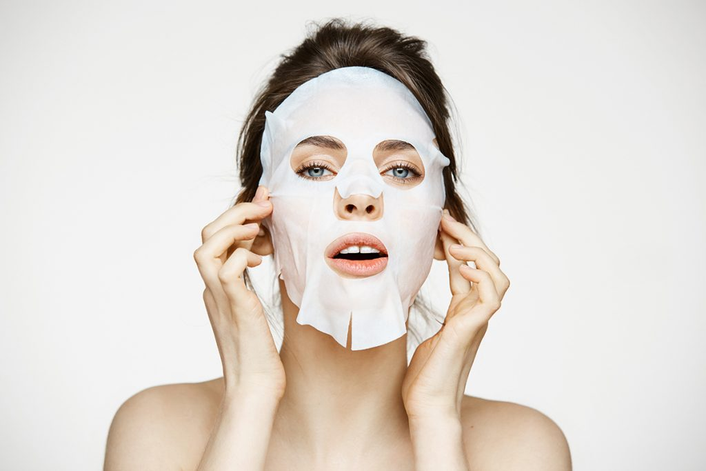 Young woman using a face mask