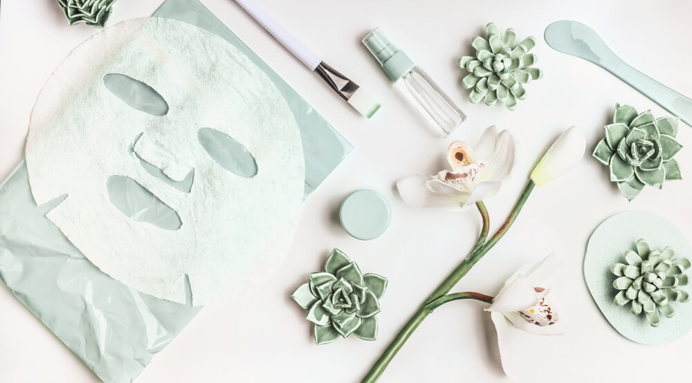 Facial sheet mask, spray bottle,and flowers on white desktop background