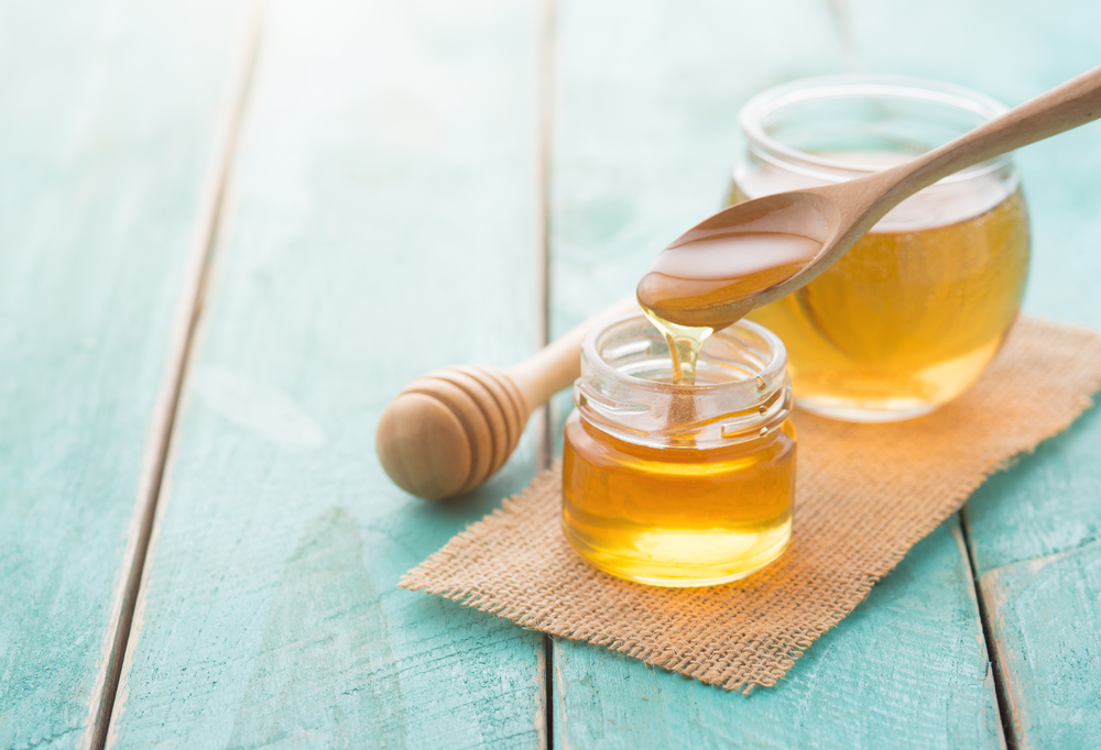 Honey with wooden honey dipper on blue wooden table