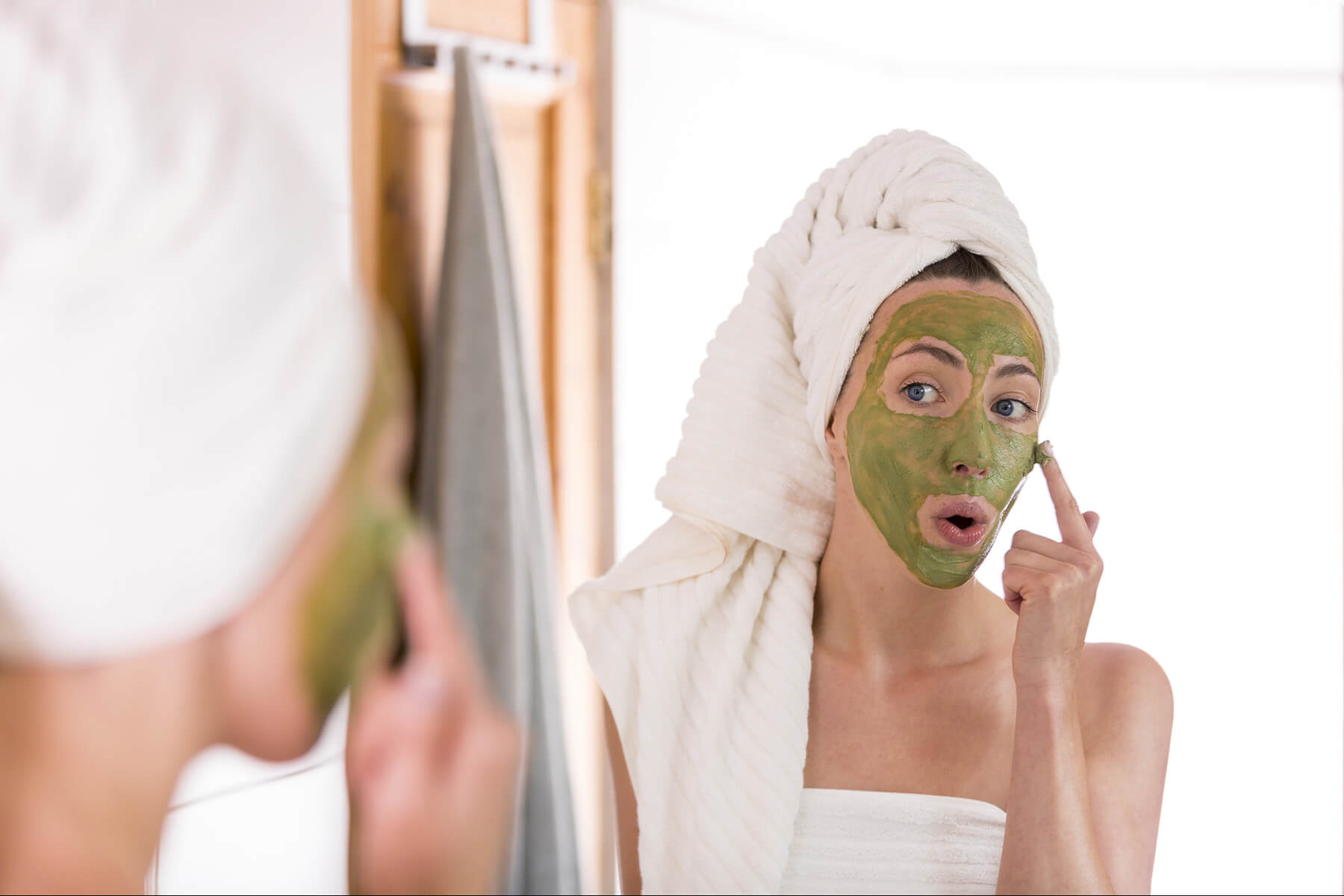 Woman applying green face mask in the mirror