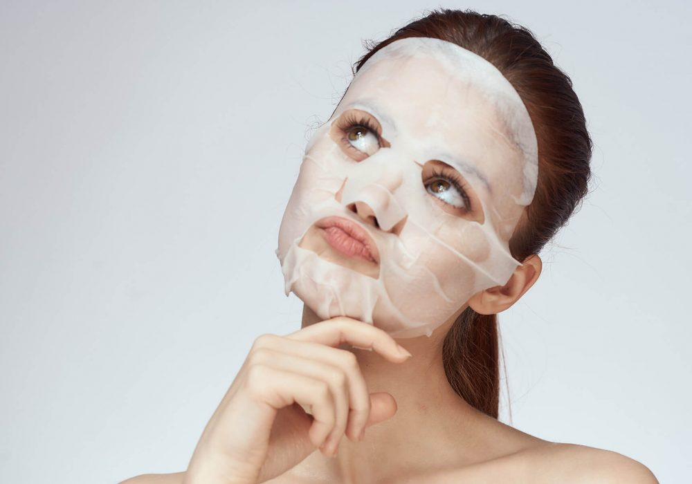 Young woman wearing a thin sheet mask
