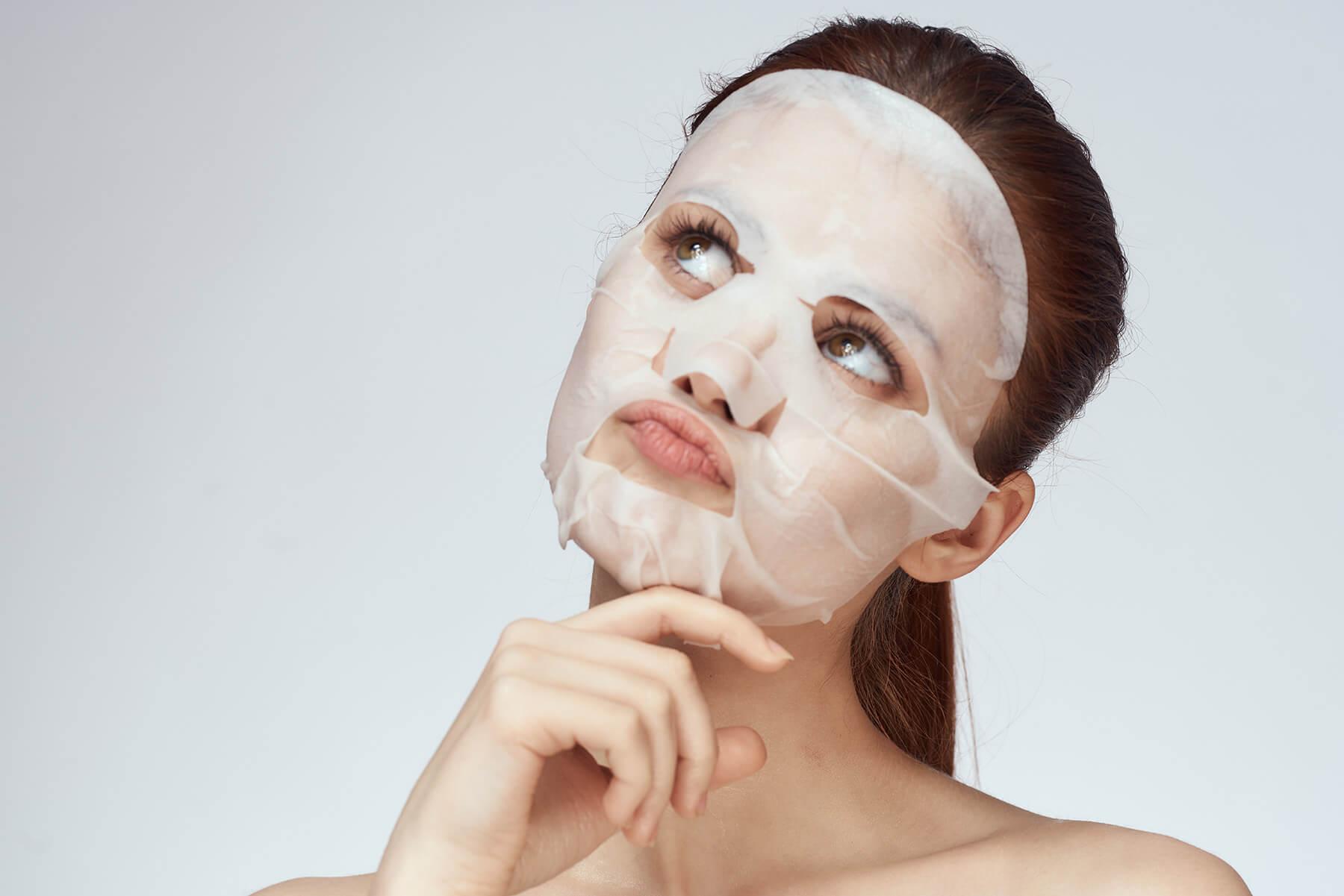 Young woman wearing a thin sheet mask