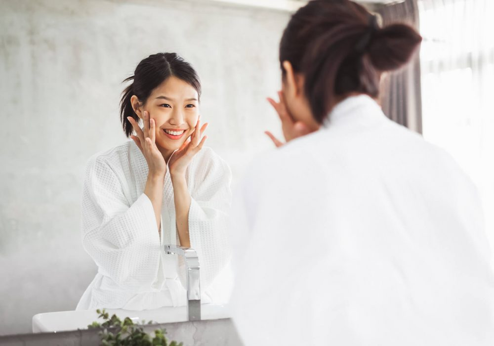 Woman cleaning her face in the mirror