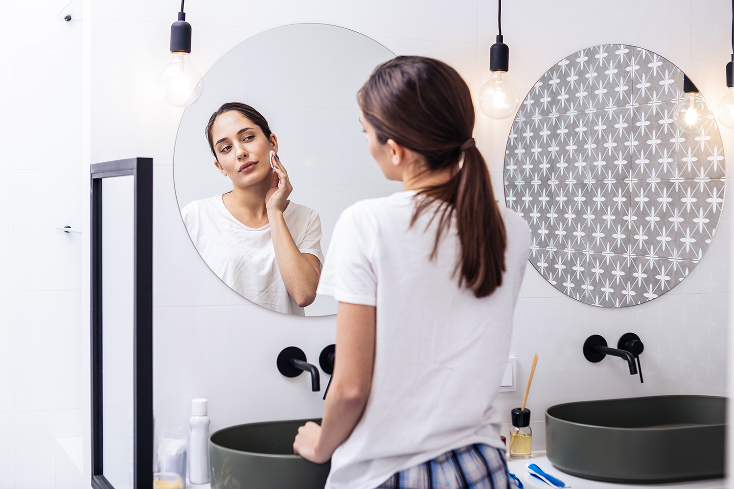 Woman moisturizing face in the mirror