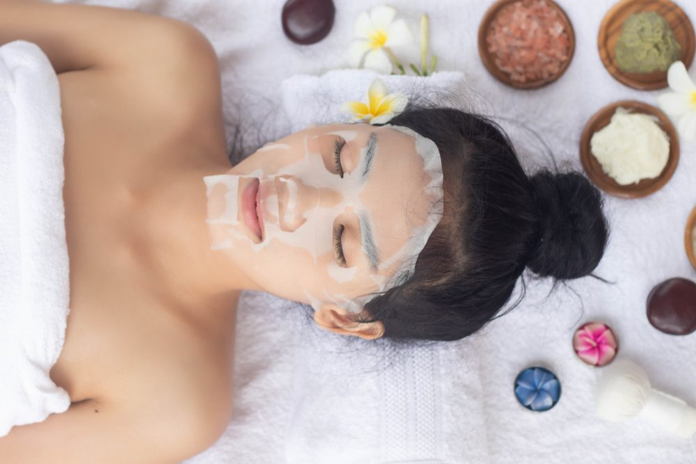 Woman using custom sheet mask with nutrients